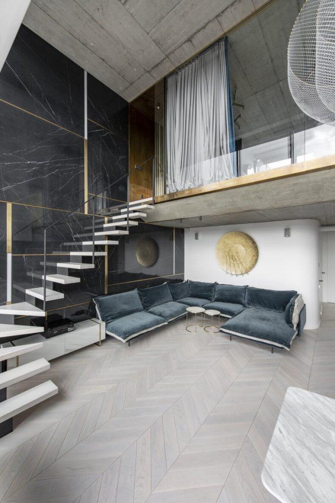 Gelungene Gegensätze: Der weiße Fußboden kontrastiert perfekt mit der schwarzen Steinwand, der rauen Betondecke und den Messingelementen.